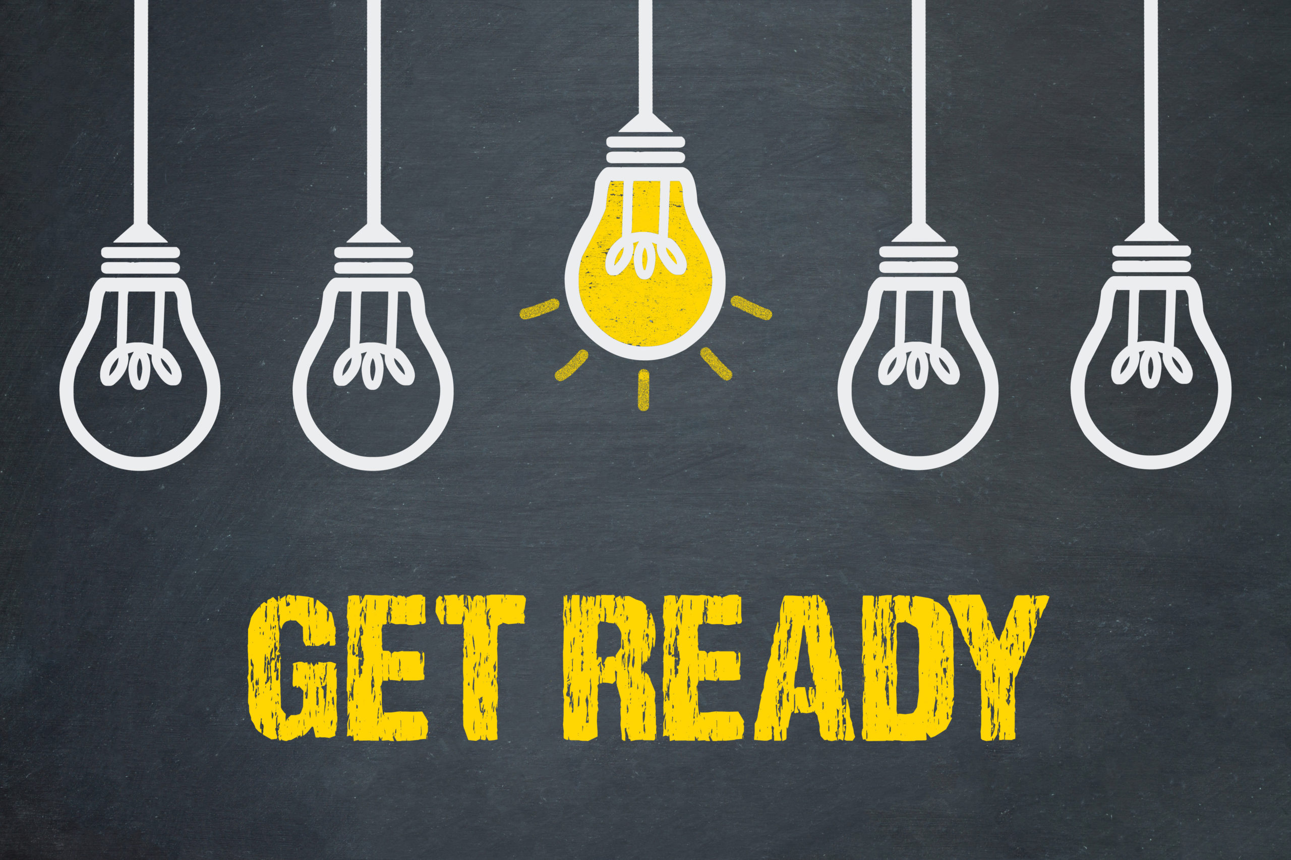 "Chalkboard sign with five hanging lightbulbs, the middle one is colored in yellow (lit), text beneath the bulbs reads, ""Get Ready"""