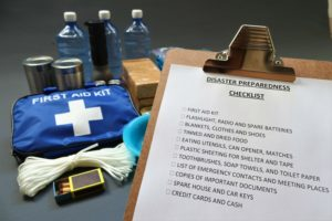 Disaster preparedness checklist on a clipboard with disaster relief items in the background. Such items would include a first aid kit,flashlight,tinned food,water,batteries and shelter.